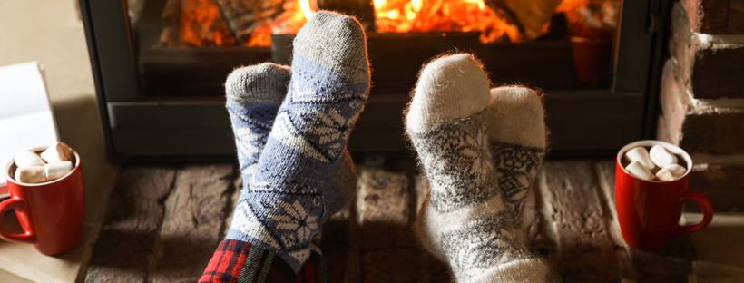 Couple wearing woolen socks, sitting in front of fireplace