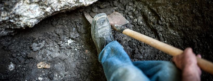 Man shoveling mud